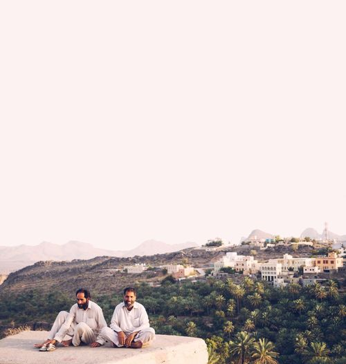 Couple sitting on mountain against clear sky