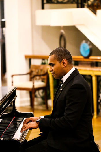 Side view of man playing piano indoors