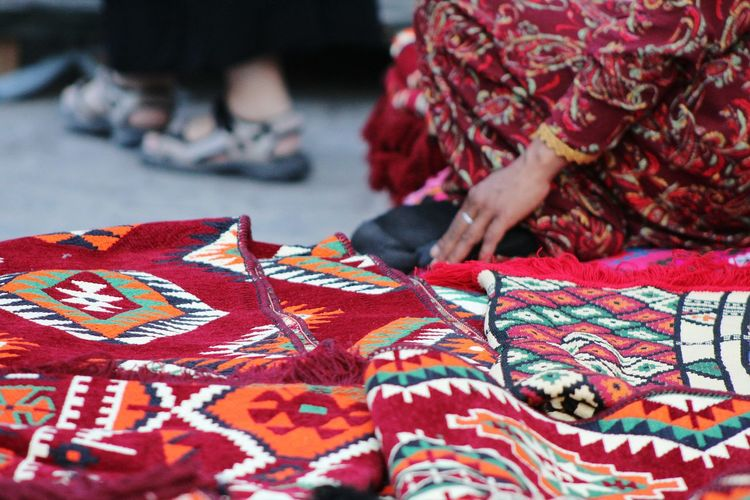 Low section of woman selling carpets