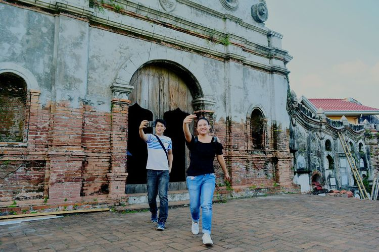 Happy friends taking selfie through smart phone while walking against historic building