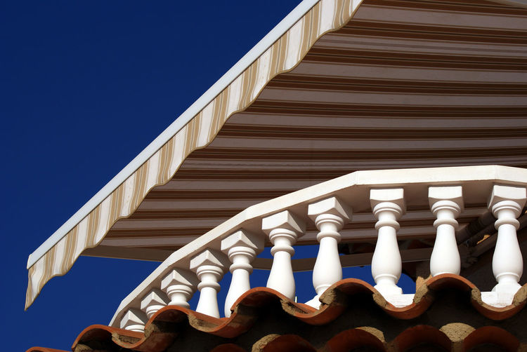 Low Angle View Of Striped Canopy Over Balcony