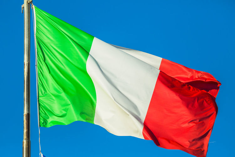 Low Angle View Of Italian Flag Against Clear Blue Sky