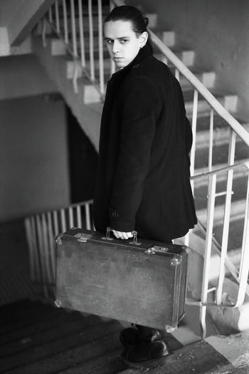 Young man holding briefcase on steps