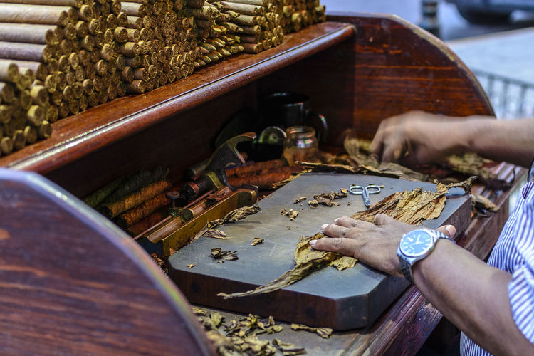 Cropped Hands Of Man Making Cigars At Table
