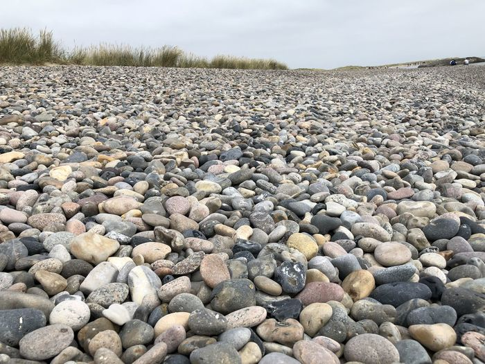 Surface level of stones on shore against sky