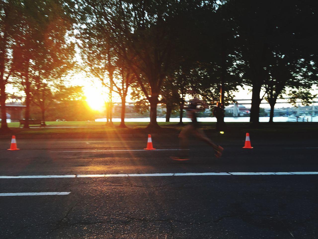 Defocused Image Of Man Running Marathon On Road By Trees