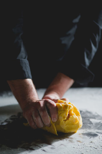 CLOSE-UP OF CHEF'S HANDS KNEADING DOUGH