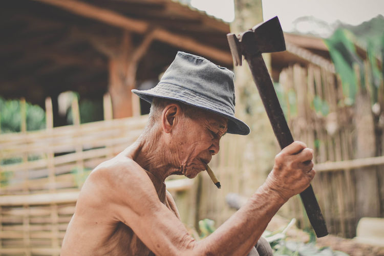 Shirtless man smoking bidi while holding hammer outdoors