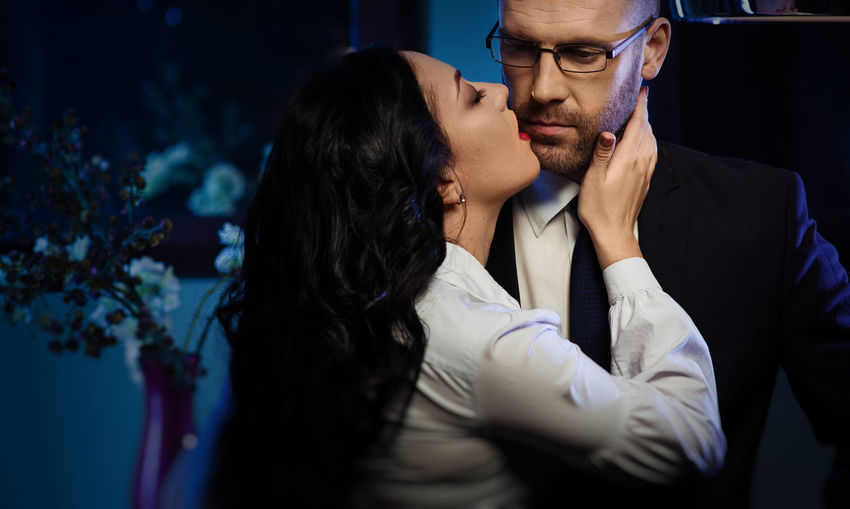 Sensuous secretary kissing businessman in office