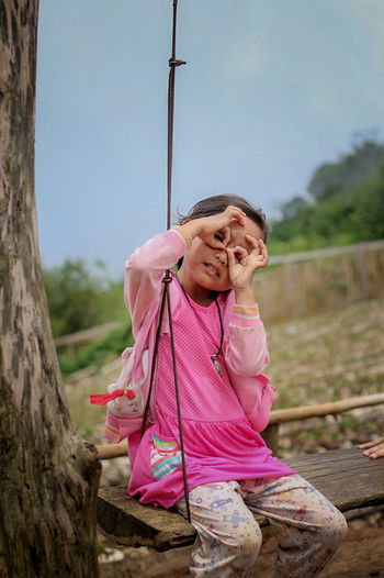 Portrait of girl gesturing while sitting on swing against sky