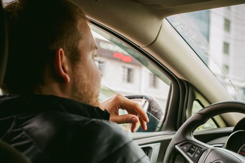 Close-Up Of Man Smoking In Car