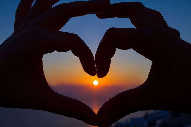 Silhouette hand holding heart shape against sky during sunset