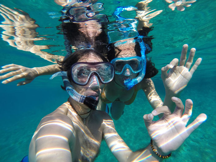 Underwater portrait of a snorkeling couple Blue Fun Leisure Activity Looking At Camera Ocean Ok Sign Outdoors Portrait Scuba Diving Scuba Mask Sea Snorkeling Swimming Swimming Goggles Transparent Water Tropical Turquoise Two People UnderSea Underwater Underwater Diving Vacations Water Young Adult Young Women