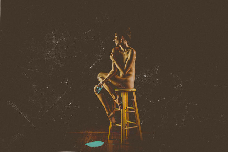 Digital composite image of people sitting on chair against black background