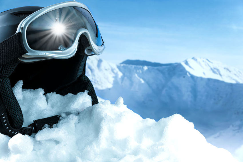 Skiing in the high mountains. Helmet and ski goggles on snow with a blue sky and mountains. Active Alpine Alps Blue Equipment Extreme Eyeglasses  Glasses Goggles Mountain Outdoors Recreational Pursuit RENT Ski Skier Sky Slope Snow Snowboard Sport Sportswear Sun Tatras Vacation Winter