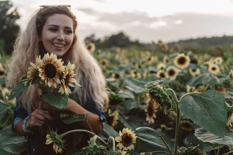 Portrait of smiling young woman with flowers in park