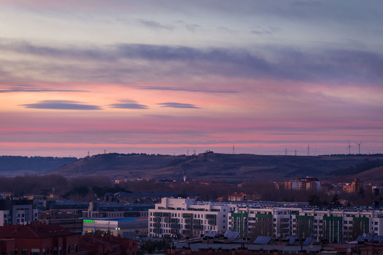 Houses In Town Against Sky During Sunset
