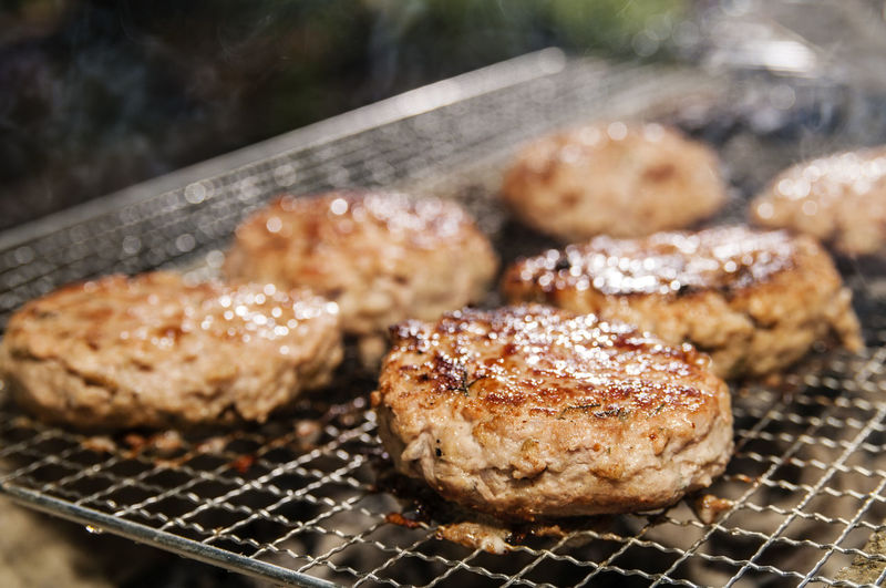 Close-Up Of Pork Burger Patties On Barbecue Grill