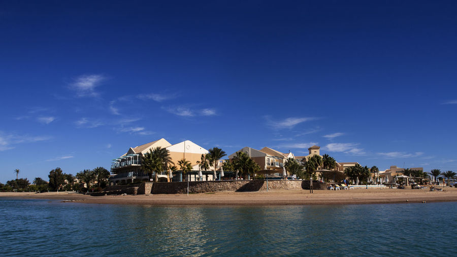 Villas on the Red Sea on a sunny day, Egypt Villas Red Sea Sunny Day Egypt Built Structure Architecture Building Exterior Water Sky Building Tree Blue Nature House No People Plant Land Residential District Outdoors Waterfront Cloud - Sky Sea