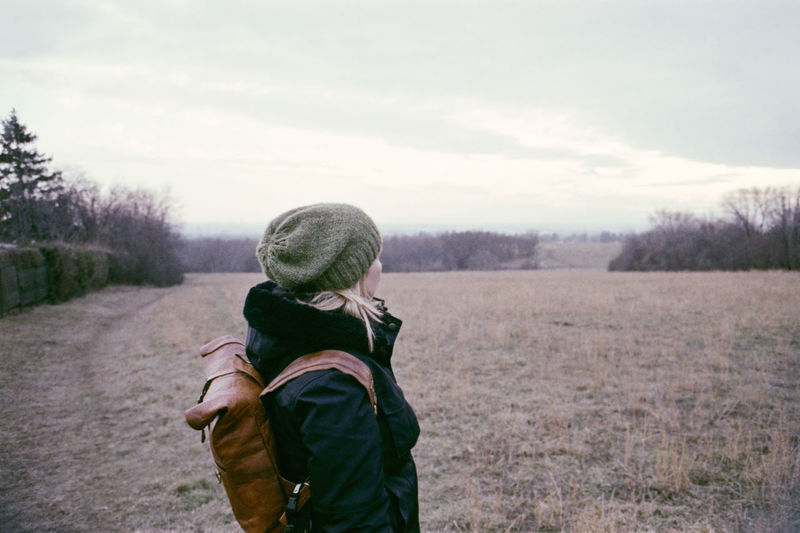 Side view of woman wearing warm clothing while standing on land against sky