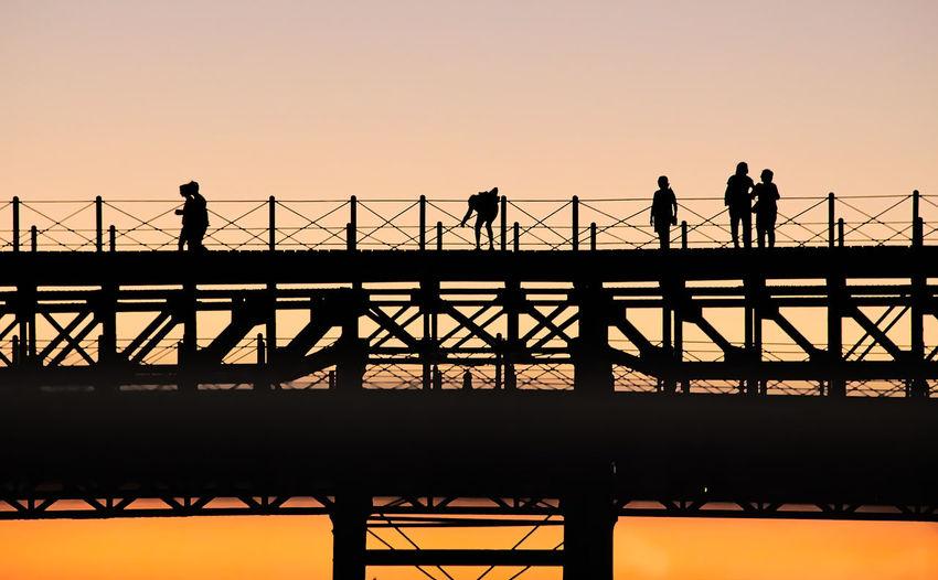 Silhouette of people on bridge against sunset