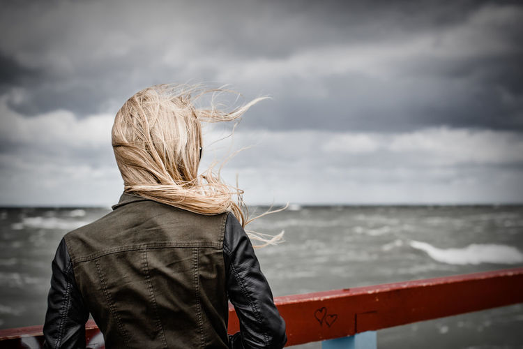 Rear view of woman looking at sea against cloudy sky