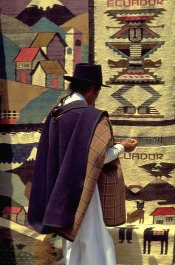 Famous for its alpaca wool textiles, the Plaza de Ponchos in Otavalo is one of the largest Indian markets in Ecuador. A weaver in the traditional costume of Otavaleno men - white trousers, poncho, and black felt hat - proudly displays his Ecuadorian textile art. Otavalo was originally a market town for the region's farming communities, but with the growth of tourism, the Saturday market is now supplies foreign tourists with handicraft souvenirs of their visit to Ecuador. http://pics.travelnotes.org Alpaca Wool Artisan Colors Ecuador Ecuadorian Textile Art Indian Indian Markets Indigenous  Market Michel Guntern Otavaleno Otavalo Plaza De Ponchos People And Places South America Souvenirs Tailored To YouTapestries Textile Art Traditional Costume Travel Travel Photography Travel Photos Travel Pics Neighborhood Map