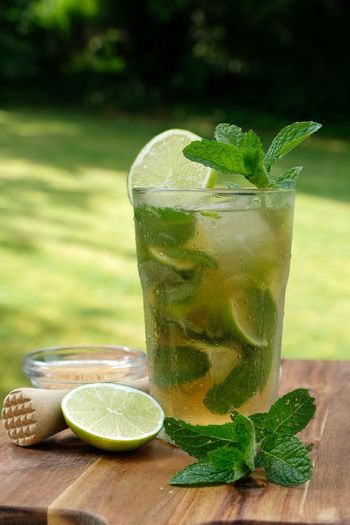 Non-alcoholic mojito summer drink nojito mocktail with wooden muddle, mint leaves on wooden board.