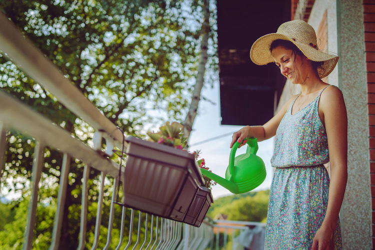 Young beautiful woman watering plants