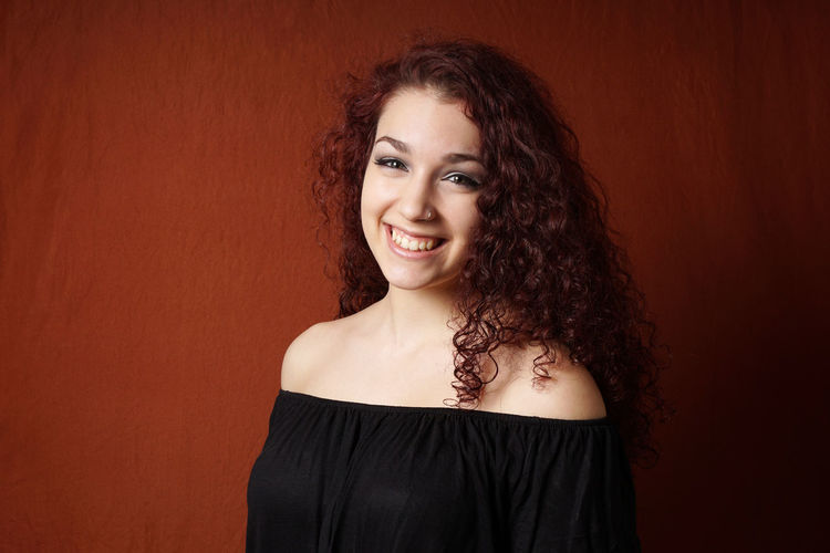 Portrait of smiling young woman against brown background
