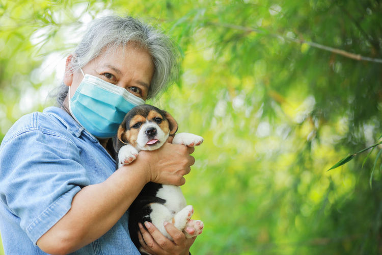 Senior woman wearing mask holding puppies standing outdoors