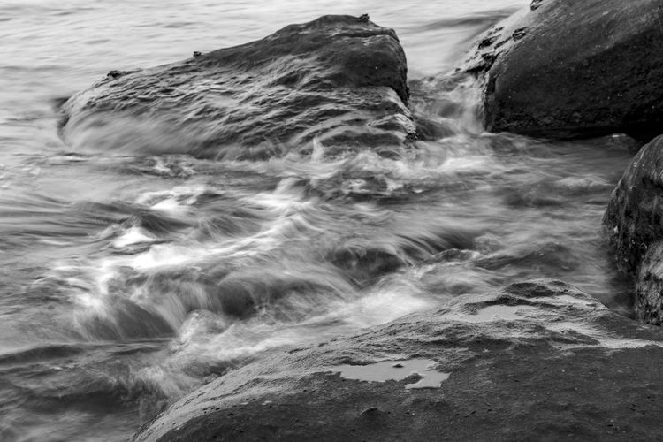 Close-up of flowing water on rock at beach