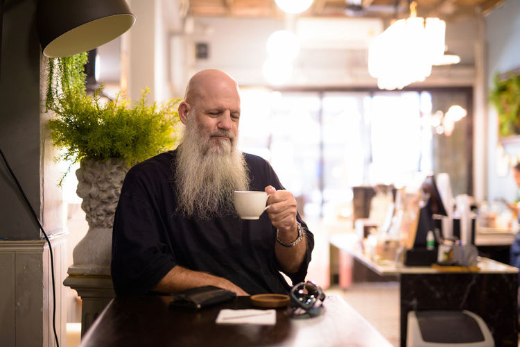 Rear view of man drinking coffee in cafe