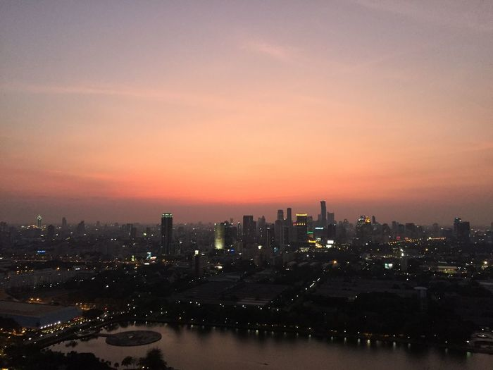River by illuminated cityscape against sky during sunset
