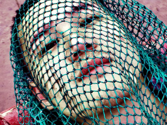 Close-Up Portrait Of Man Covered In Net