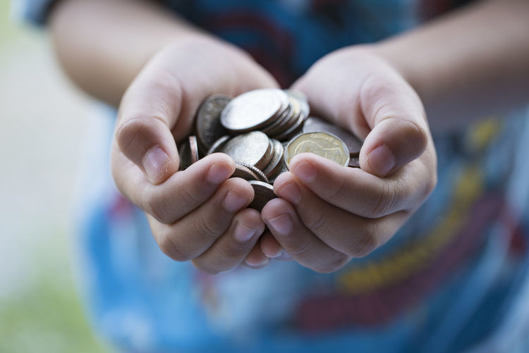 Midsection Of Child Holding Coins Outdoors