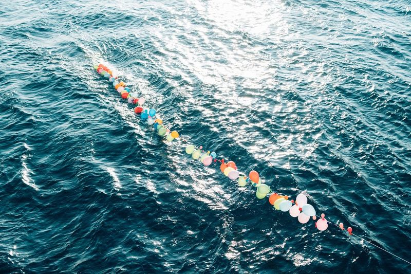 High Angle View Of Balloons In Sea