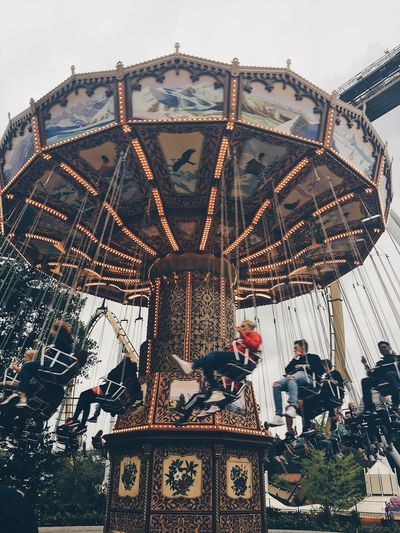 Low angle view of people at amusement park against sky