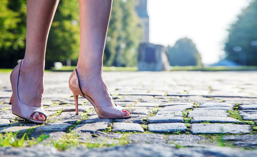 Low Section Of Woman Wearing High Heels Standing On Footpath