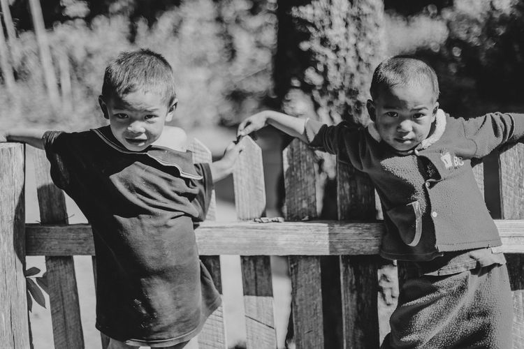Portrait of siblings standing by fence