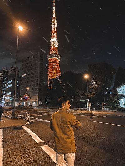 Full length of man standing on street against illuminated buildings in city