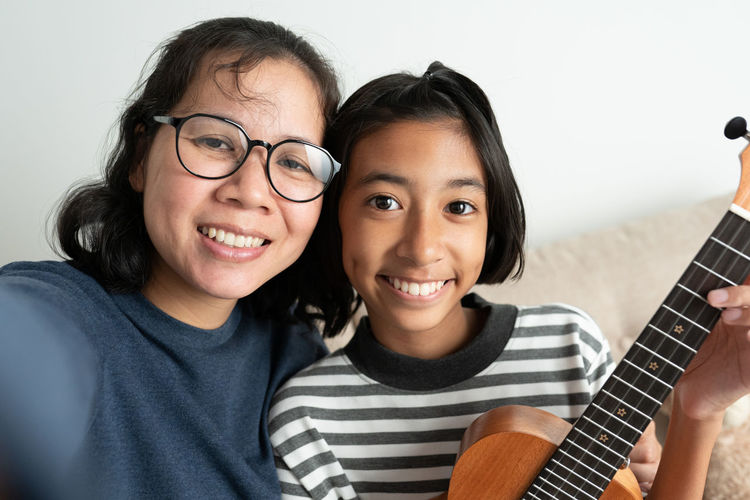 Close-up portrait of happy woman with daughter playing ukulele at home