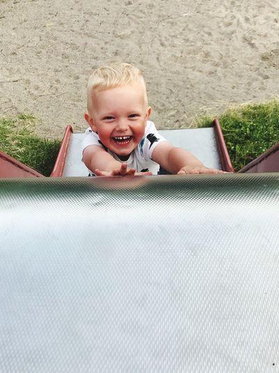 High Angle Portrait Of Happy Boy Sliding Down Slide At Playground