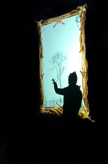 Rear view of silhouette girl looking through window