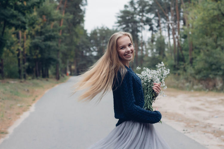 Portrait Of Young Woman Holding Bouquet While Standing On Road Amidst Trees