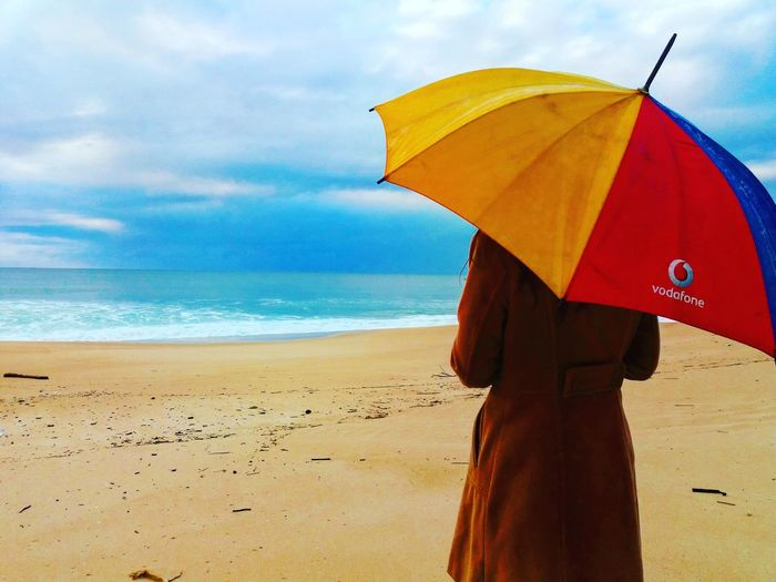 Umbrella Protection Rain Beach Weather Standing Sea People Adult Horizon Over Water One Person Holding Water Cloud - Sky Human Body Part Thunderstorm Outdoors Adults Only Smiling Young Adult Beauty Tranquility Portugal Is Beautiful Portugal Praiadagale