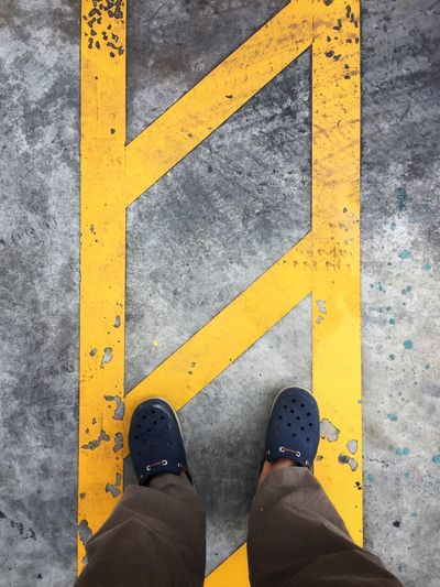Lines are drawn on the road for guidance and directions. A concept of road safety. Yellow Standing Low Section One Person Human Leg Human Body Part Shoe Real People Personal Perspective Outdoors Day Close-up One Man Only People Safety First!