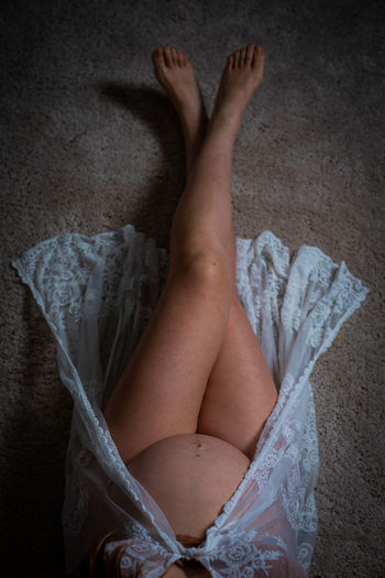 Low section of woman lying on bed