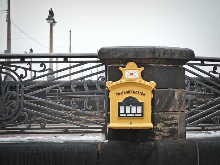 Mailbox on footbridge against clear sky