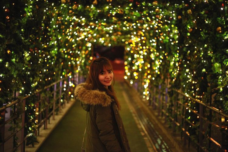 Close-up of smiling girl on illuminated christmas tree at night